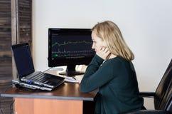 Arbeit über eine Börse Aufpassende Änderungen der Geschäftsfrau im Geldumtauschdiagramm lizenzfreies stockfoto