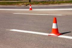 Arbeit über Straße Fokus auf dem zentralen Kegel Handeln Sie Kegel, mit den weißen und orange Streifen auf Asphalt Straße und Ver Lizenzfreies Stockbild