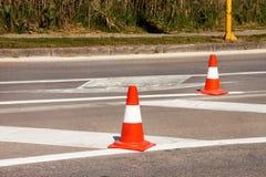Arbeit über Straße Fokus auf dem zentralen Kegel Handeln Sie Kegel, mit den weißen und orange Streifen auf Asphalt Straße und Ver Stockfotos