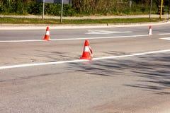 Arbeit über Straße Fokus auf dem zentralen Kegel Handeln Sie Kegel, mit den weißen und orange Streifen auf Asphalt Straße und Ver Stockbild