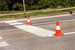 Arbeit über Straße Fokus auf dem zentralen Kegel Handeln Sie Kegel, mit den weißen und orange Streifen auf Asphalt Straße und Ver Stockbilder