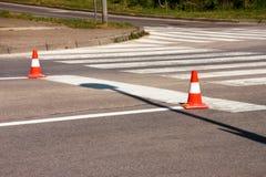 Arbeit über Straße Fokus auf dem zentralen Kegel Handeln Sie Kegel, mit den weißen und orange Streifen auf Asphalt Straße und Ver Lizenzfreie Stockfotografie