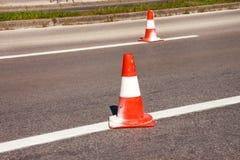 Arbeit über Straße Fokus auf dem zentralen Kegel Verkehrskegel, mit Weiß und O Lizenzfreie Stockfotos