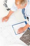Arbeit des älteren Mannes über Lichtpauseaufbaupläne Lizenzfreies Stockbild
