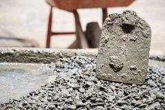 Arbeit mischt cemen, Wasser, versanden zusammen für Bau sitzen Lizenzfreie Stockbilder