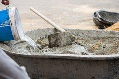 Arbeit mischt cemen, Wasser, versanden zusammen für Bau sitzen Stockfotos