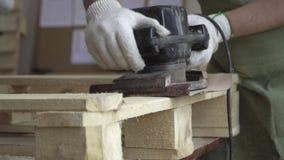 Arbeit mit hölzernen Strukturen und Schleifmaschine Verarbeitung von hölzernen Produkten durch den Meister in den weißen Handschu stock video footage