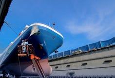 Arbeit in sich hin- und herbewegendem Trockendock mit Wasserstrahl säubert den Bord lizenzfreie stockfotografie