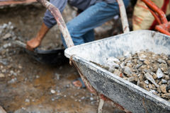 Arbeit und Schubkarre mit Kiesel an der Baustelle Lizenzfreies Stockfoto