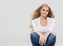 Arbeiten blonde Jeans des gelockten Haares der Schönheit Sitzen in voller Länge auf Boden um Stockfotografie