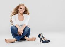 Arbeiten blonde Jeans des gelockten Haares der Schönheit Sitzen in voller Länge auf Boden um Stockfotos