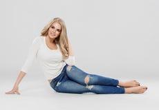 Arbeiten blonde Jeans des gelockten Haares der Schönheit Sitzen in voller Länge auf Boden um Lizenzfreies Stockbild