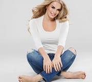 Arbeiten blonde Jeans des gelockten Haares der Schönheit Sitzen in voller Länge auf Boden um Stockbilder