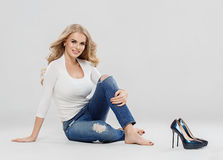 Arbeiten blonde Jeans des gelockten Haares der Schönheit Sitzen in voller Länge auf Boden um Lizenzfreie Stockfotos