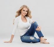 Arbeiten blonde Jeans des gelockten Haares der Schönheit Sitzen in voller Länge auf Boden um Stockfoto