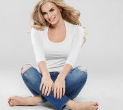 Arbeiten blonde Jeans des gelockten Haares der Schönheit Sitzen in voller Länge auf Boden um Stockbild