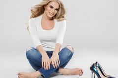 Arbeiten blonde Jeans des gelockten Haares der Schönheit Sitzen in voller Länge auf Boden um Lizenzfreie Stockfotografie