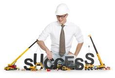 Arbeiten an Erfolg: Buildinging Erfolgwort des Geschäftsmannes. Stockbild