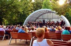 Arbeiten hörendes klassisches Musikkonzert der Leute im Park im Garten Lizenzfreie Stockfotos