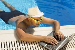 Arbeiten an Laptop vom Swimmingpool stockbilder