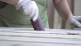 Arbeiten mit Holz Rolle des Sandpapiers und Verarbeitung von Holzbalken Hölzerne Produkte werden durch den Meister herein verarbe stock video