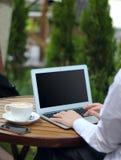 Arbeiten mit Laptop im Kaffee Lizenzfreie Stockfotos