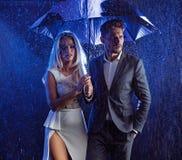 Arbeiten Sie Artporträt eines Paares um, das im regnerischen Wetter aufwirft lizenzfreie stockbilder
