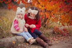 Arbeiten Sie Babys Schwestern stilvolles gekleidetes brunnette und blonde tragende warme die Herbstkleidungsjackenaufstellung um, Lizenzfreie Stockfotos