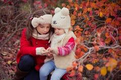 Arbeiten Sie Babys Schwestern stilvolles gekleidetes brunnette und blonde tragende warme die Herbstkleidungsjackenaufstellung um, Stockfotografie
