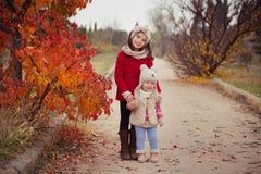 Arbeiten Sie Babys Schwestern stilvolles gekleidetes brunnette und blonde tragende warme die Herbstkleidungsjackenaufstellung um, Stockbild