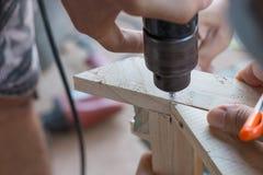 Arbeiten Sie bei bohrender Holzarbeit mit elektrischer Bohrmaschine zusammen Stockfoto