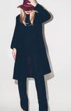 Arbeiten Sie bezauberndes blondes Modell in einem schwarzen Mantel und in einem Hut um Fallgewinn stockfotografie
