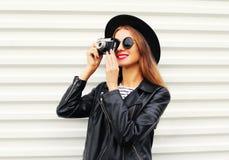 Arbeiten Sie Blick, Modell der recht jungen Frau mit der Retro- Filmkamera um, die eleganten Hut, lederne Felsenjacke über Weiß t Stockfotografie