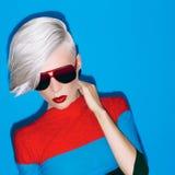 Arbeiten Sie blonde Dame mit modischer Frisur und Sonnenbrille auf einem Blauen um Lizenzfreie Stockfotografie