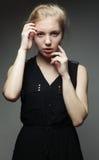 arbeiten Sie blonde Frau im schwarzen Kleid um, das im Studio aufwirft Lizenzfreie Stockbilder