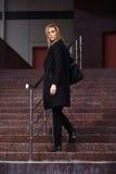 Arbeiten Sie blonde Frau im schwarzen Mantel auf den Schritten um Stockbilder
