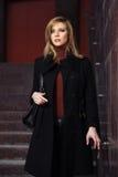 Arbeiten Sie blonde Frau im schwarzen Mantel auf den Schritten um Lizenzfreie Stockfotografie
