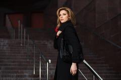 Arbeiten Sie blonde Frau im schwarzen Mantel auf den Schritten um Lizenzfreies Stockfoto