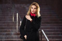 Arbeiten Sie blonde Frau im schwarzen Mantel auf den Schritten um Lizenzfreie Stockfotos