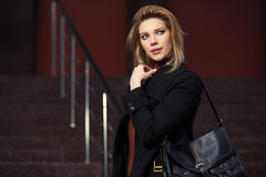 Arbeiten Sie blonde Frau im schwarzen Mantel auf Nachtstadtstraße um Stockfotografie