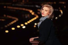 Arbeiten Sie blonde Frau im schwarzen Mantel in einer Nachtstadtstraße um Lizenzfreie Stockbilder
