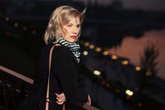 Arbeiten Sie blonde Frau im schwarzen Mantel in einer Nachtstadtstraße um Stockbilder