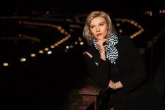 Arbeiten Sie blonde Frau im schwarzen Mantel in einer Nachtstadtstraße um Lizenzfreies Stockfoto