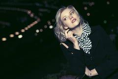 Arbeiten Sie blonde Frau im schwarzen Mantel in einer Nachtstadtstraße um Lizenzfreie Stockfotografie