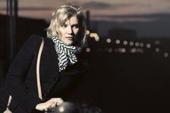 Arbeiten Sie blonde Frau im schwarzen Mantel in einer Nachtstadtstraße um Stockbild