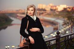 Arbeiten Sie blonde Frau im schwarzen Mantel mit der Handtasche um, die auf Zaun sich lehnt Lizenzfreie Stockfotografie