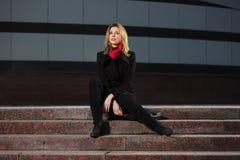 Arbeiten Sie blonde Frau im schwarzen Mantel um, der auf den Schritten sitzt Lizenzfreies Stockbild