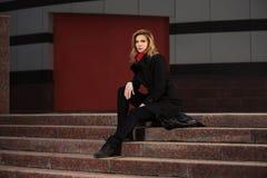 Arbeiten Sie blonde Frau im schwarzen Mantel um, der auf Schritten sitzt Stockfoto