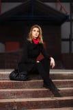 Arbeiten Sie blonde Frau im schwarzen Mantel um, der auf Schritten sitzt Lizenzfreie Stockfotografie