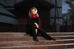 Arbeiten Sie blonde Frau im schwarzen Mantel um, der auf Schritten sitzt Lizenzfreies Stockfoto